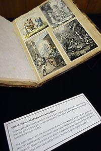 Open album on display, showing four drawings or paintings pasted onto the righthand page, with descriptive text card visible at bottom of image.
